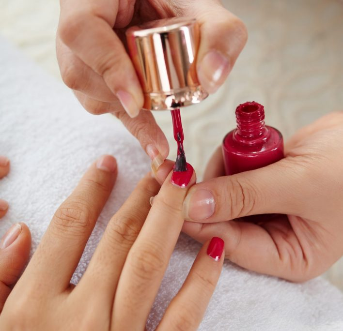 Master applying bright color to nails of woman